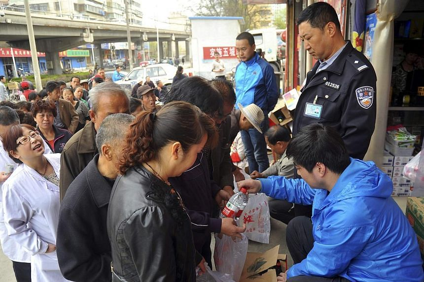 People line up to buy bottled water outside a store in Lanzhou, Gansu province, on April 11, 2014. Authorities in the eastern Chinese city of Jingjiang have suspended water supplies after quality abnormalities were detected, state media said on Frida