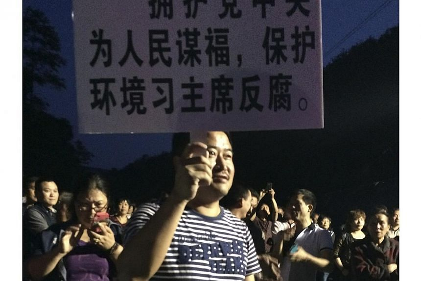 A demonstrator holds a placard during a protest against the construction of a waste incinerator in Hangzhou, Zhejiang province on May 7, 2014. Chinese experts have defended the construction of a huge waste incinerator in the scenic eastern city of Ha