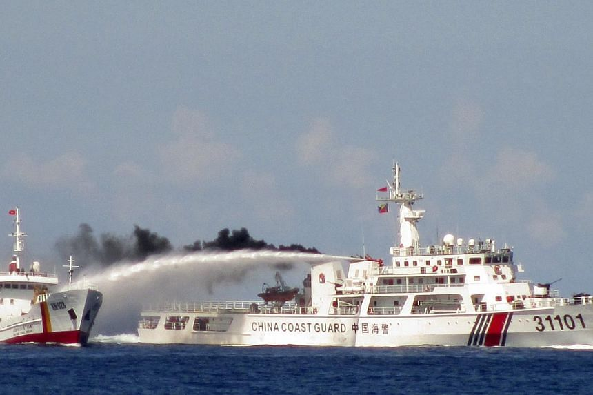 A Chinese ship (right) uses water cannon on a Vietnamese Sea Guard ship on the South China Sea near the Paracels islands, in this handout photo taken on May 3, 2014. China's foreign ministry blamed the United States on Friday for stoking tensions in