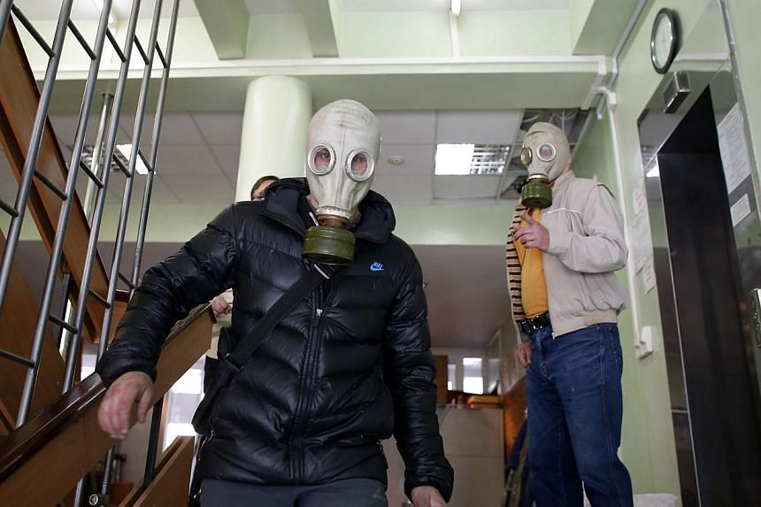 Pro-Russia rebels wearing gas masks walk inside the city hall in Mariupol, eastern Ukraine on May 7, 2014. Fighting broke out on Friday in Ukraine's south-eastern port city of Mariupol, causing casualties, according to reports by Ukrainian and Russia
