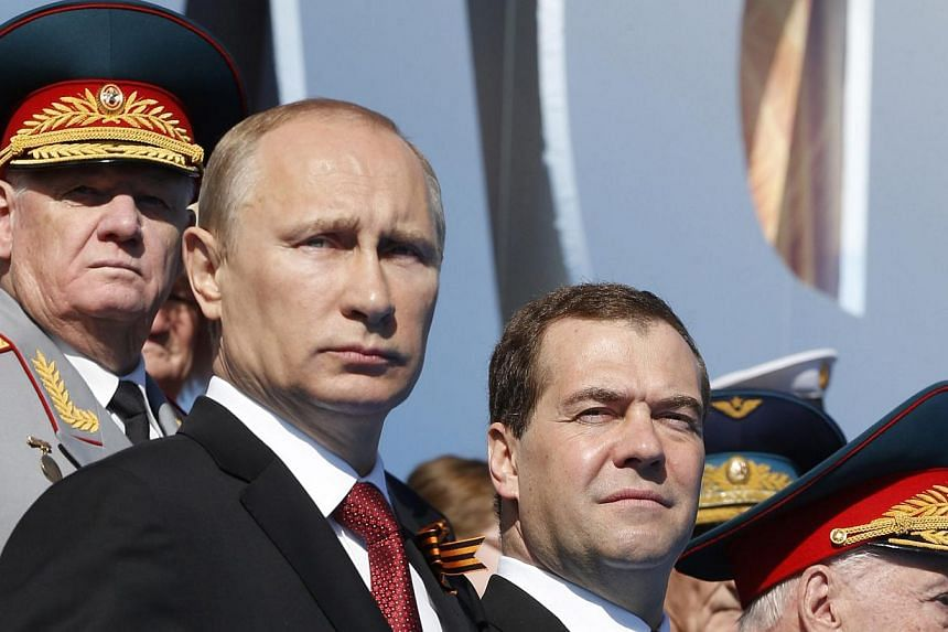 Russian President Vladimir Putin (front left) and Russian Prime Minister Dmitry Medvedev (front centre) attend a military parade marking the 69th anniversary of the victory over the Nazi Germany in the WWII in the Red Square in Moscow, Russia on May