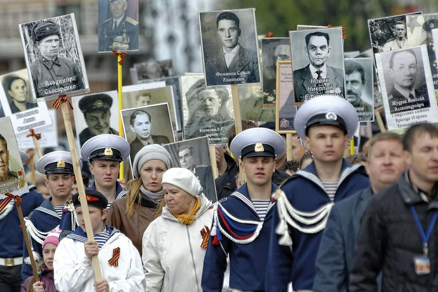 Russian servicemen and cadets march with portraits of relatives who took part in World War 2 during a parade to mark Victory day in Vladivostok on May 9, 2014. Thousands of Russian troops on Friday marched in Red Square to mark 69 years since victory