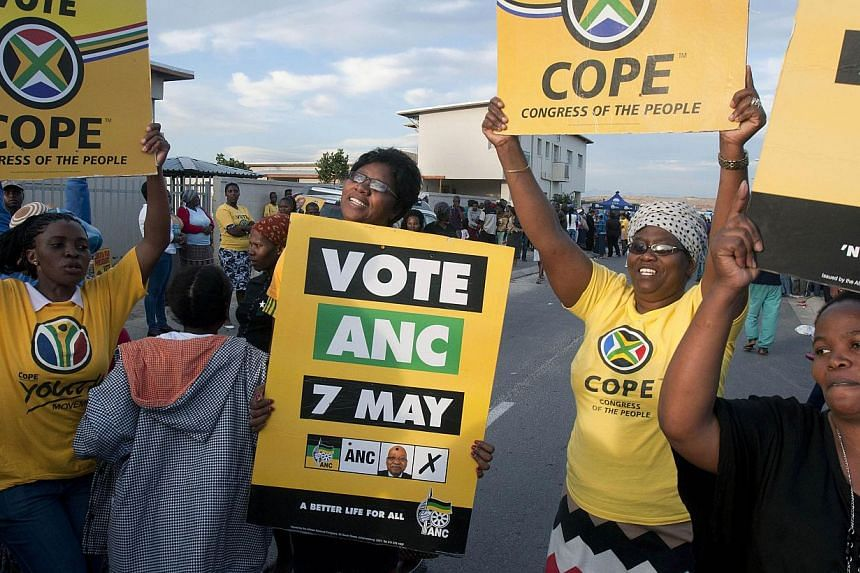 Supporters of the ruling African National Congress (ANC) and opposing Congress of the People (COPE) sing and dance together next to a polling station in the Vrygrond informal settlement on May 7, 2014, as South Africa held its fifth post-apartheid ge