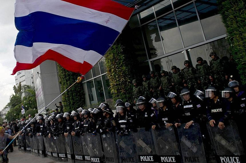 A Thai anti-government protester waves a large national flag as Thai riot-policemen stand guard at the entrance of a television station during an anti-government rally in Bangkok on May 9, 2014. -- PHOTO: AFP