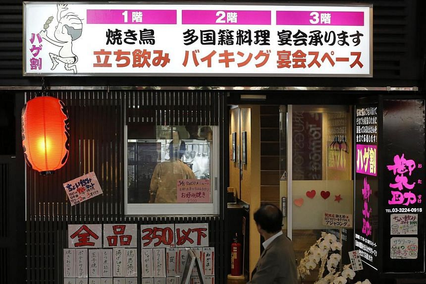 """A man walks past the Otasuke """"izakaya"""" style pub and restaurant in Tokyo on May 8, 2014.Bald is beautiful at a new Tokyo restaurant, where follicularly challenged customers are welcomed with open arms and offered discounts not available to thei"""