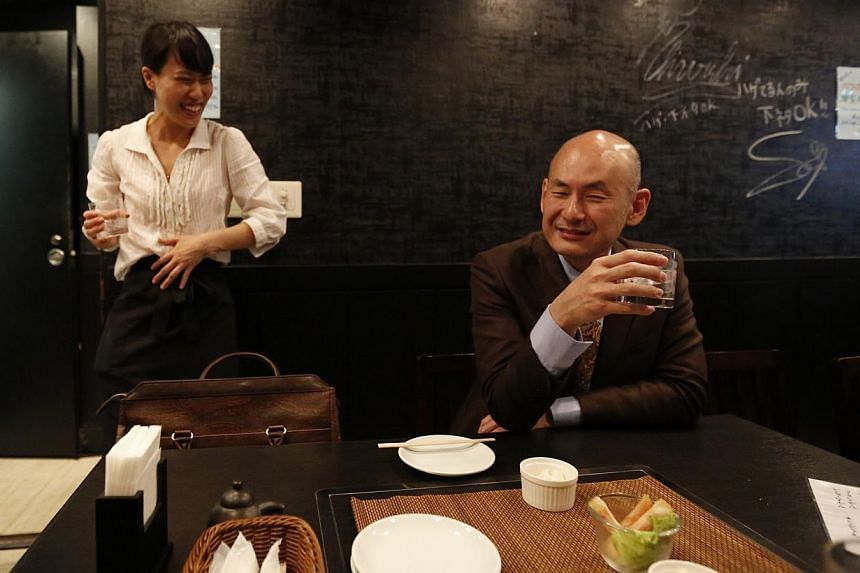 "Shiro Fukai, 48, drinks distilled spirit next to manager Yoshiko Toyoda (left) at the Otasuke ""izakaya"" style pub and restaurant in Tokyo on May 8, 2014. -- PHOTO: REUTERS"