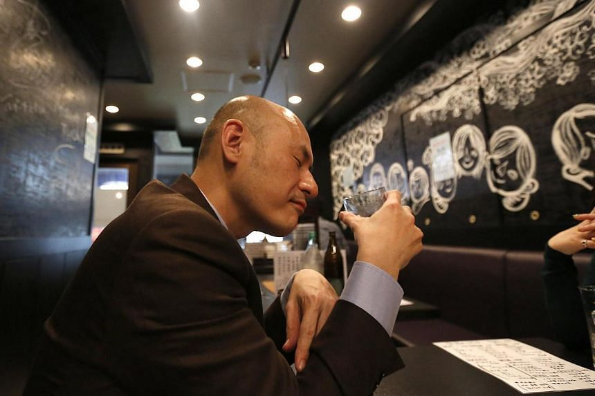"Shiro Fukai, 48, drinks distilled spirit at the Otasuke ""izakaya"" style pub and restaurant in Tokyo on May 8, 2014. -- PHOTO: REUTERS"