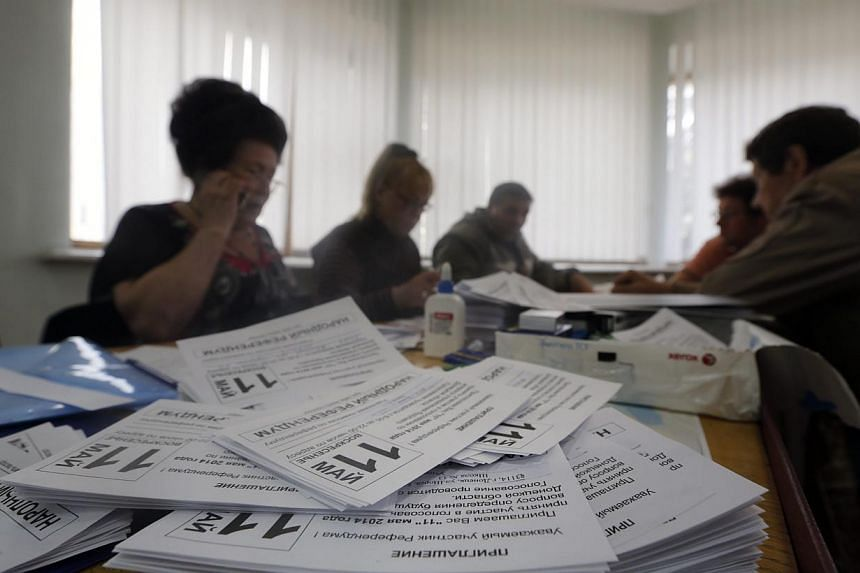 Members of the self-declared Donetsk People's Republic commission prepare a polling station in Donetsk, Ukraine on May 8, 2014. Sitting around a horseshoe table, half a dozen bouffant-haired ladies work away with scissors and glue on piles of freshly