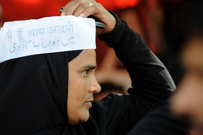 A supporter of Aam Aadmi Party (AAP) wears the white colour Gandhi cap emblazoned with the words 'I am Aam Aadmi' (I am Common Man) in Hindi and Urdu during a rally in Mumbai. --PHOTO: AFP