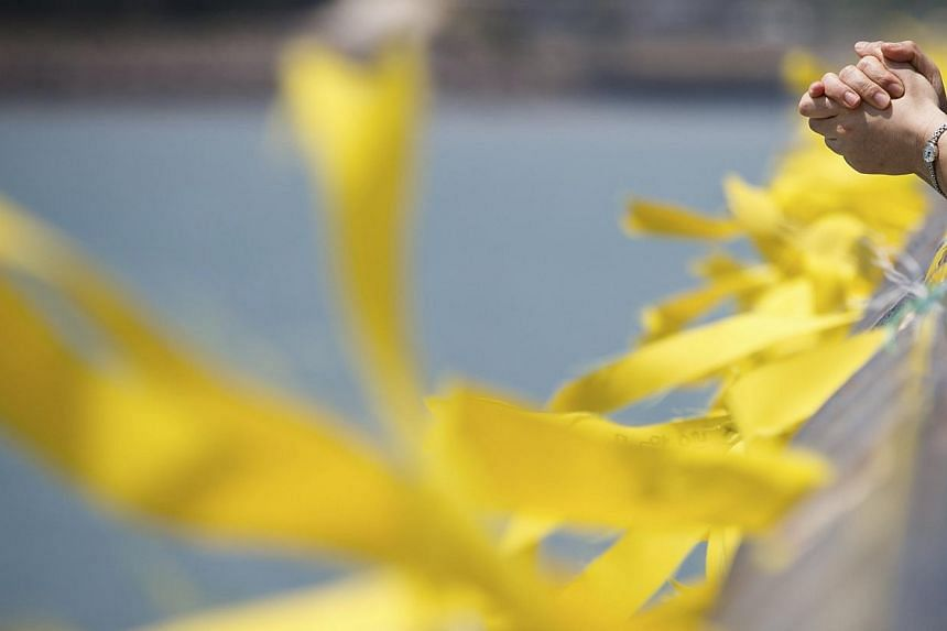 A family member of a missing passenger onboard the sunken Sewol ferry prays near yellow ribbons dedicated to the dead and missing passengers tied to a railing at a port in Jindo on May 9, 2014. -- PHOTO: REUTERS