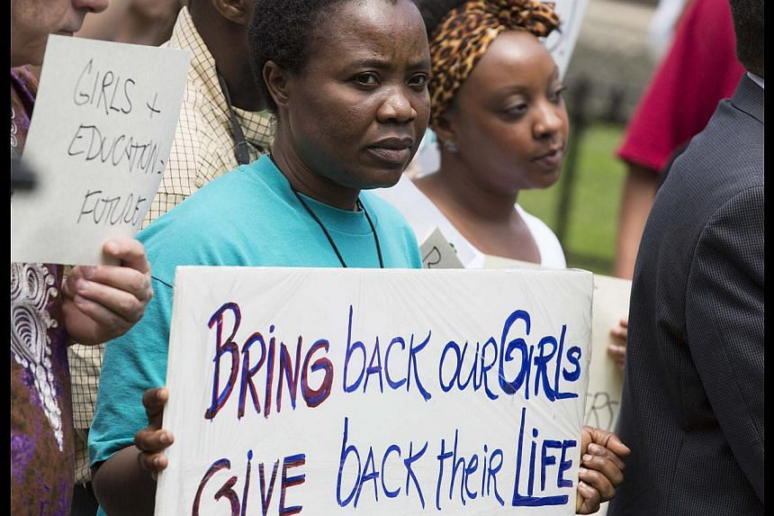 Women hold signs during a vigil held in the wake of the kidnapping of more than 200 Nigerian schoolgirls by the Islamist militant group Boko Haram, in Washington on May 9, 2014. -- PHOTO: REUTERS