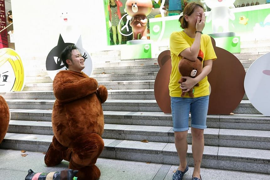 "Mr Alex Wee threw a surprise wedding proposal to his girlfriend, Ms Cheryl Foo, by disguising himself in a Line mascot called ""Brown"" outside the Line pop-up store. -- ST PHOTO: ONG WEE JIN"