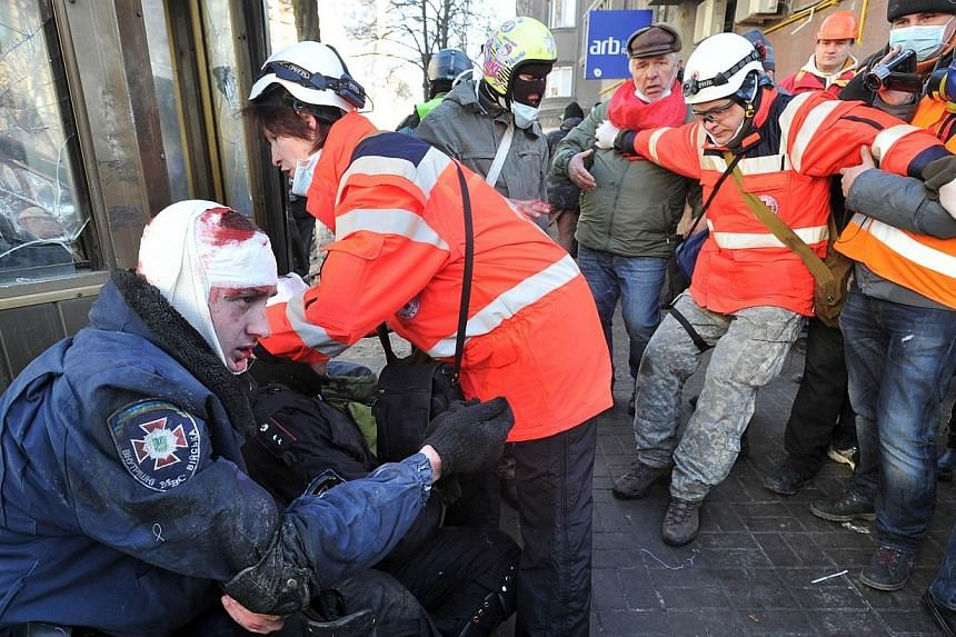Red Cross workers give first aid to policemen wounded during clashes with anti-government protester in Kiev on February 18, 2014. Several members of the Red Cross have been arrested in the rebel-held eastern Ukrainian city of Donetsk on suspicio