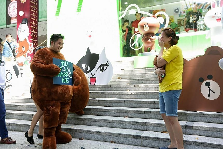 """Mr Alex Wee threw a surprise wedding proposal to his girlfriend, Ms Cheryl Foo, both of whom are huge LINE fans, by disguising himself in a Line mascot called """"Brown"""" outside the Line pop-up store outside Wisma Atria. -- ST PHOTO:ONG WEE JIN"""