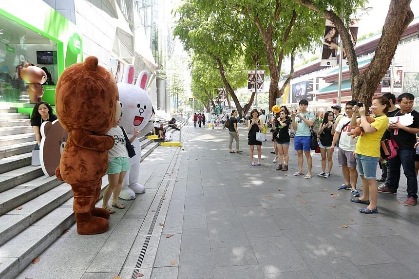 Ms Cheryl Foo, (right, in yellow), taking a photo of the Line mascots outside Wisma Atria. -- ST PHOTO:ONG WEE JIN