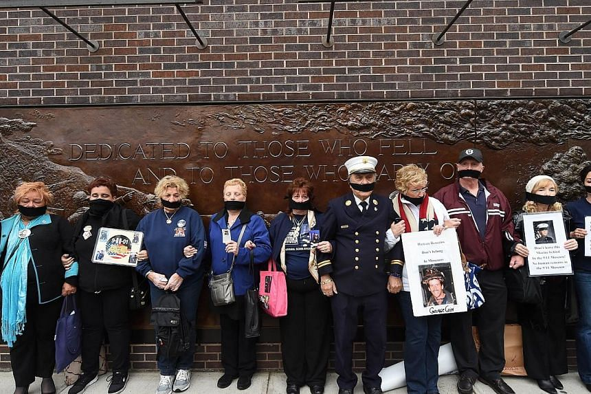 Relatives of victims of the Sept 11, 2001, attacks stage a protest, as unidentified remains of some of the victims in the attacks are escorted to a repository at Ground Zero in New York, on May 10, 2014. -- PHOTO: AFP