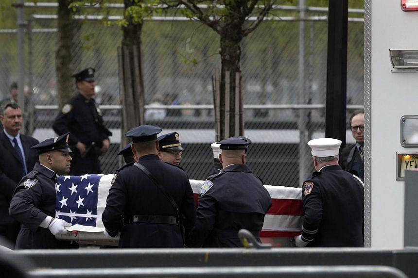 A casket carrying the unidentified remains of victims of the Sept 11, 2001, attacks is escorted to a repository at Ground Zero in New York, US, on May 10, 2014. -- PHOTO: EPA