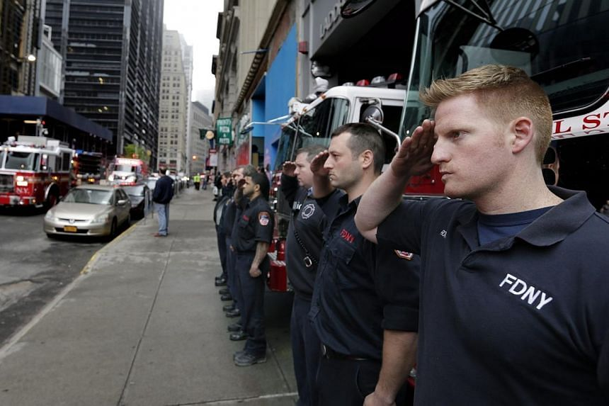 New York City fireman from Ladder Company 10 Engine Company 10 adjacent to the World Trade Center site, stand and salute the motorcade carrying the unidentified remains of victims of the Sept 11, 2001, attacks is escorted to a repository at Ground Ze