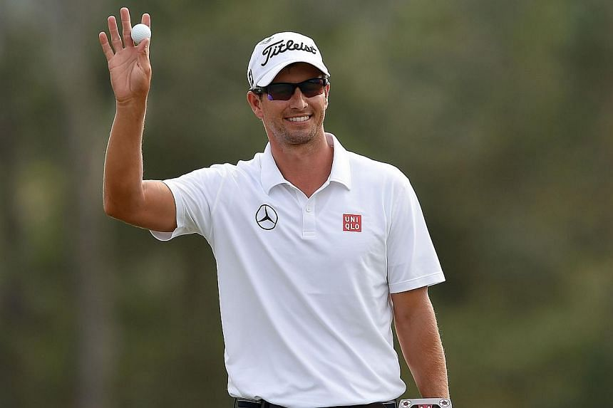 This file photo taken on April 13, 2014 shows Adam Scott of Australia reacting after putting on the 18th green during the final round of the 78th Masters Golf Tournament at Augusta National Golf Club in Augusta, Georgia. Adam Scott made the cut