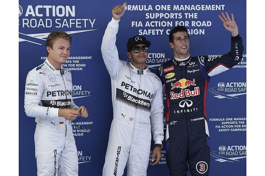 (Left to right) Mercedes-AMG's German driver Nico Rosberg, Mercedes-AMG's British driver Lewis Hamilton and Red Bull Racing's Australian driver Daniel Ricciardo celebrate in the parc ferme after the qualifying session at the Circuit de Catalunya on M