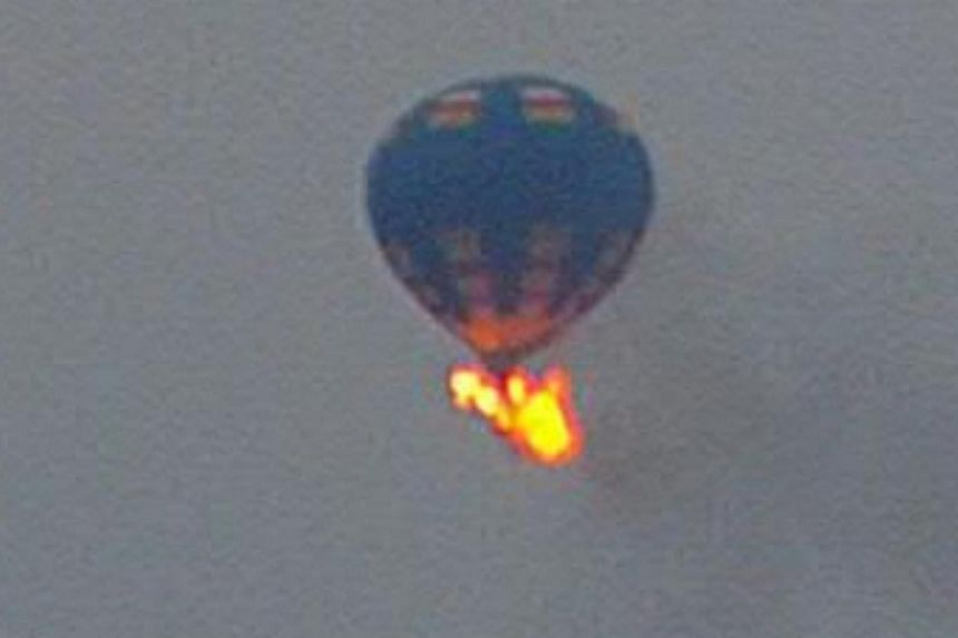 A hot air balloon that took off with at least three people on board caught fire and crashed on Friday evening in Virginia. -- PHOTO: NANCY JOHNSON/ INSTAGRAM