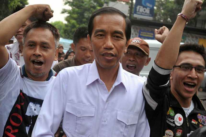 In this picture taken on April 11, 2014, popular presidential candidate of main the opposition party Indonesian Democratic Party of Struggle (PDI-P) and Jakarta Governor Joko Widodo (centre) walks with his supporters in Jakarta following the April 9,