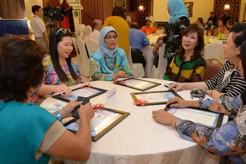 Madam Halimah (centre) chatting with some judges (from left) OCBC remisier Jenny Yeo; People Association's Women Integration Network Council chairman Joanna Portilla; Singapore Council of Women's Organisations president Laura Hwang; Mrs Mary Hoe-Tan,