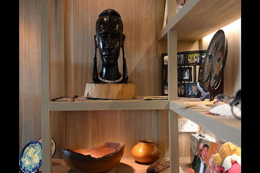 Clean lines (right) and a woody palette (far right) give the flat of Ms Catherine Cheung and Mr Elvin Too (both above) an earthy touch. Sliding panels (left) let the home owners open or close off this nook when necessary. Souvenirs from their travels