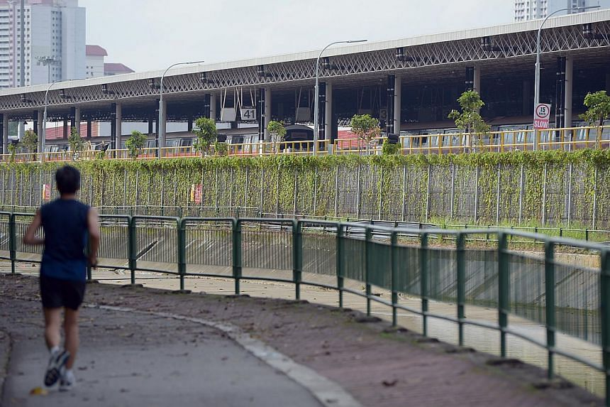 A man jogs past the SMRT Bishan depot which has reinforced steel fences. This is one of the measures SMRT has taken to beef up security after past lapses in May 2010 and August 2011. -- ST FILE PHOTO: DESMOND WEE