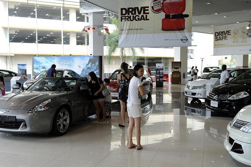 Customers checking out cars at Tan Chong Motor's Ubi showroom. -- BT FILE PHOTO:BRYAN VAN DER BEEK
