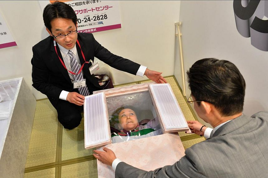 A woman lies in a coffin at a funeral fair in the Grand Generation's Collection 2014 produced by Japanese retailer Aeon in Makuhari on April 11, 2014. Japanese are spending less on funerals as more people opt for simpler and therefore less expensive