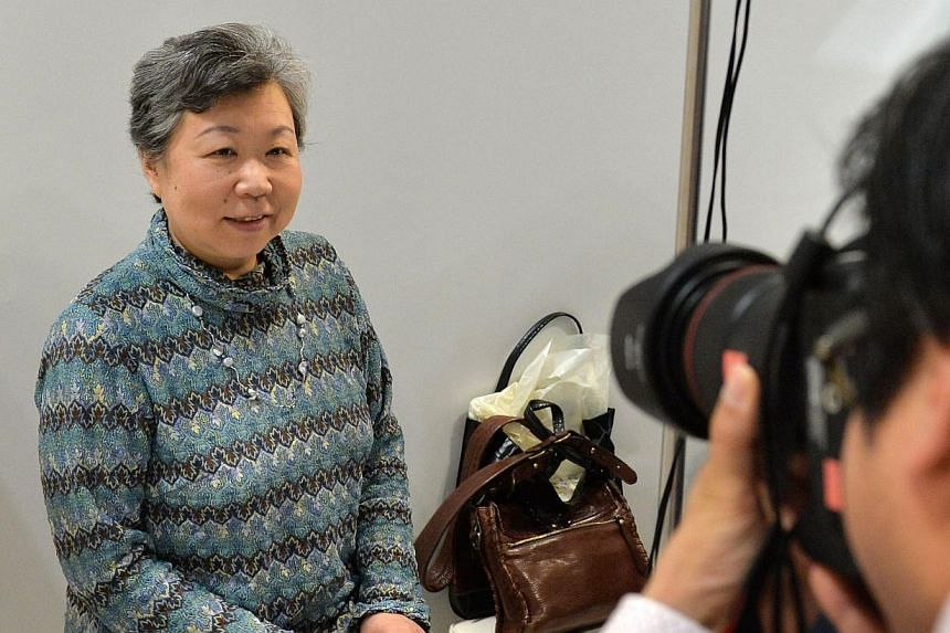 A woman poses for a photograph to be used for her deceased portrait at a funeral fair in the Grand Generation's Collection 2014 produced by Japanese retailer Aeon in Makuhari on April 11, 2014. -- PHOTO: AFP