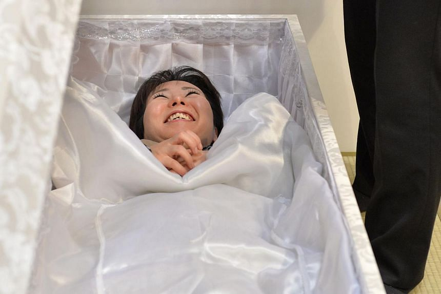 A woman lies in a coffin at a funeral fair in the Grand Generation's Collection 2014 produced by Japanese retailer Aeon in Makuhari on April 11, 2014. Japanese are spending less on funerals as morepeople opt for simpler and therefore less expen