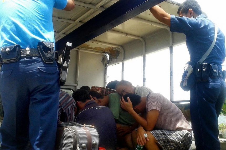 In this photo taken on May 8, 2014, two Philippine police officers guard the 11 crew members of a Chinese-flagged fishing vessel as they are transported by truck to the town of Taytay on the western Philippine island of Palawan. The suspects were arr