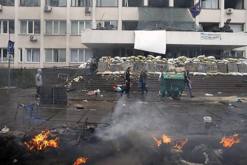People walk near a burning barricade outside the city hall in south-eastern port city of Mariupol on May 9, 2014. Tension was running at fever pitch in eastern Ukraine on Saturday on the eve of an independence referendum, as rebels briefly held sever