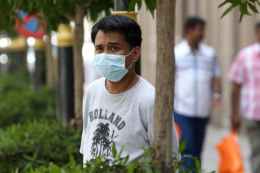 An Asian man wears a mouth and nose mask as he walks in a street of the Red Sea coastal city of Jeddah on April 27, 2014. Saudi Arabia announced seven more deaths from the Mers coronavirus on Saturday, as the World Health Organisation prepared f