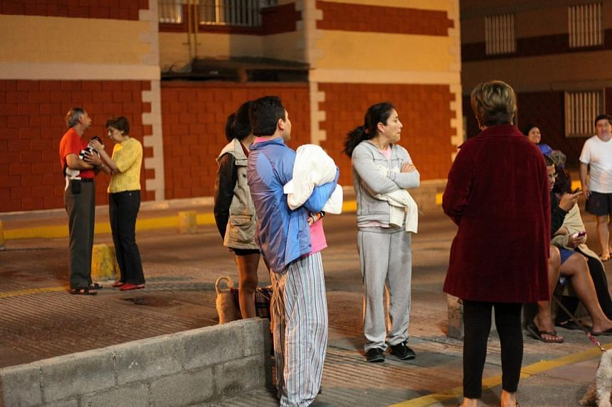 Residents wait for news outside their houses after a 5.9 magnitude earthquake shook Mexico City, in Mexico, early May 10, 2014.A strong 6.0-magnitude earthquake shook southern Mexico and the capital early on Saturday, two days after a similar t