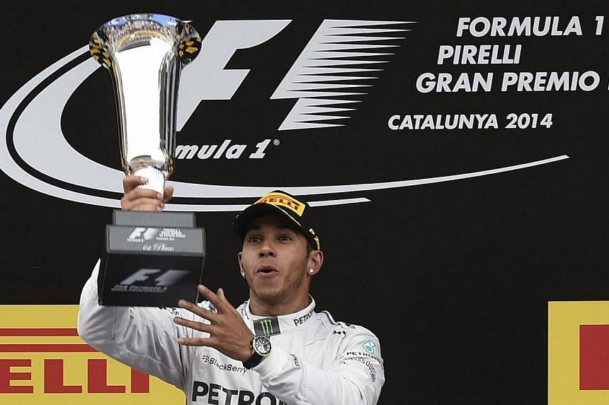 Mercedes-AMG's British driver Lewis Hamilton celebrates on the podium after the Spanish Formula One Grand Prix on May 11, 2014, at the Circuit de Catalunya in Montmelo on the outskirts of Barcelona. -- PHOTO: AFP
