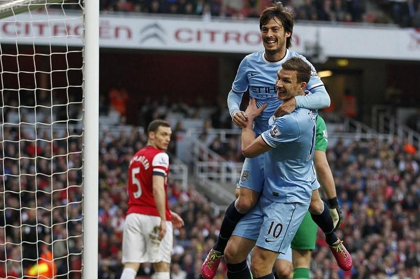 Manchester City's midfielder David Silva (centre) celebrates scoring a goal with teammate Edin Dzeko during the English Premier League (EPL) match between Arsenal and Manchester City at the Emirates Stadium in London on March 29, 2014. Manchester Cit