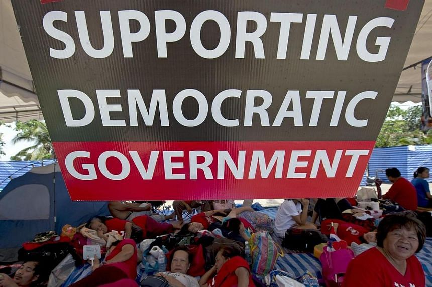 "Thai pro-government ""Red Shirts"" protesters attend a rally to support the government in Bangkok on May 11, 2014. Thailand's authorities warned on Sunday, May 11, 2014, that opposition efforts to hand power to an unelected regime risked unleashin"