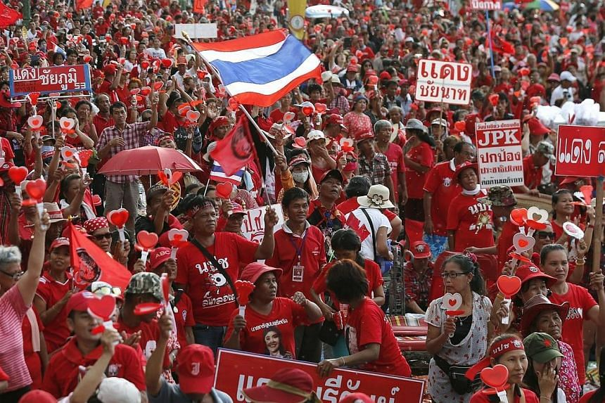 """Thai pro-government Red Shirt protesters stage a rally on the outskirts of Bangkok, Thailand on May 11, 2014.South-east Asia's regional bloc called on Sunday, May 11, 2014, for a """"peaceful resolution"""" to the political crisis gripping Thailand,"""