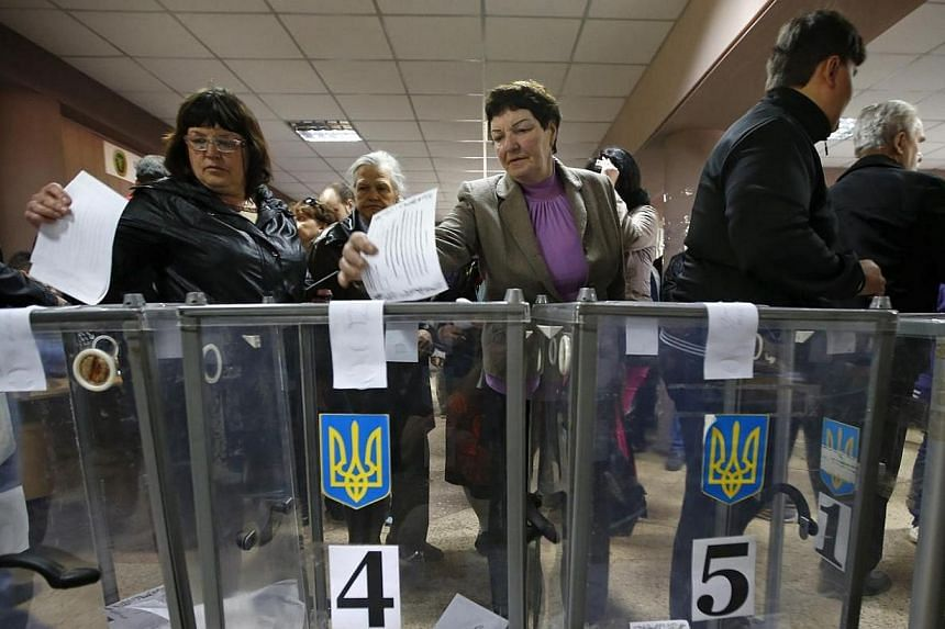People visit a polling station to take part in a referendum on the status of Donetsk region in the eastern Ukrainian city of Mariupol on May 11, 2014. Voting began on Sunday, May 11, 2014, in referendums called by pro-Russian rebels in eastern U