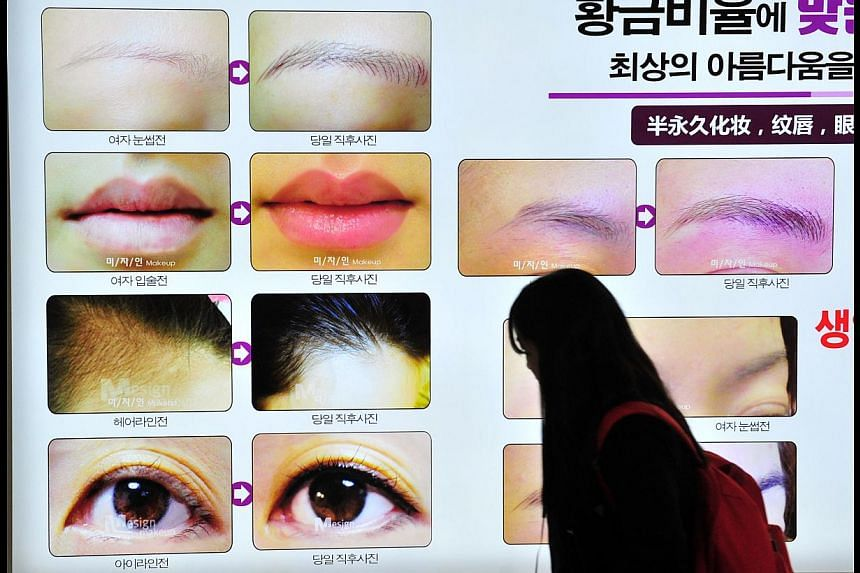 A pedestrian walking past an advertisement for a plastic surgery clinic in Seoul. South Korea has become a hot plastic surgery destination for Singapore residents. But many are reporting botched operations.