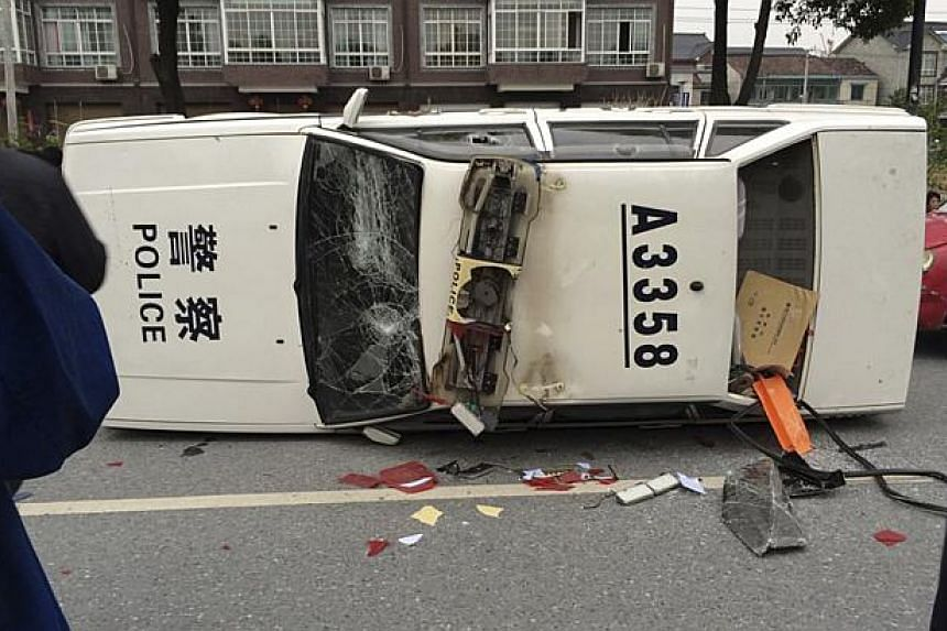 A police car is seen smashed and overturned as demonstrators protest against the construction of a waste incinerator, in the Yuhang district of Hangzhou, Zhejiang province on May 10, 2014. -- PHOTO: REUTERS