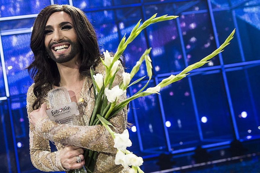 Conchita Wurst representing Austria poses with the trophy after winning the Eurovision Song Contest 2014 Grand Final in Copenhagen, Denmark, on May 10, 2014. -- PHOTO: EPA