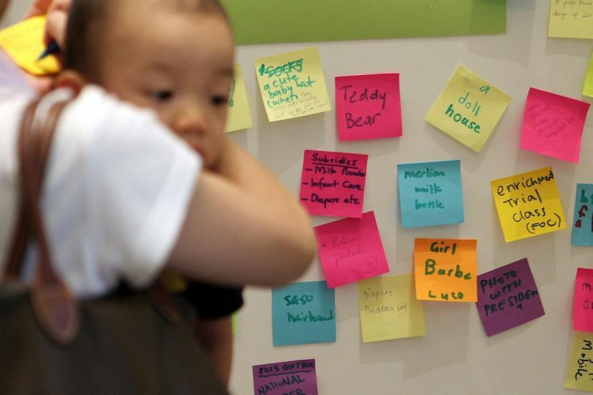 A woman putting up her suggestion for the Jubilee Baby Gift package at VivoCity on April 13, 2014. All Singaporeans born next year will be issued a special edition birth certificate with a commemorative mark as part of the Jubilee Baby Gift bundle to