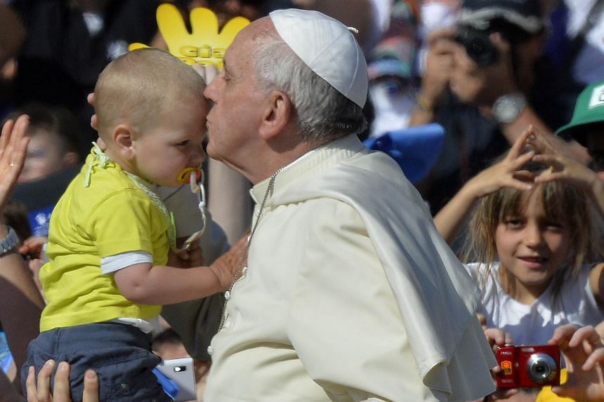 Pope Francis kisses a child as he arrives for an audience with Catholic schools at St Peter's square at the Vatican on May 10, 2014. -- PHOTO: AFP