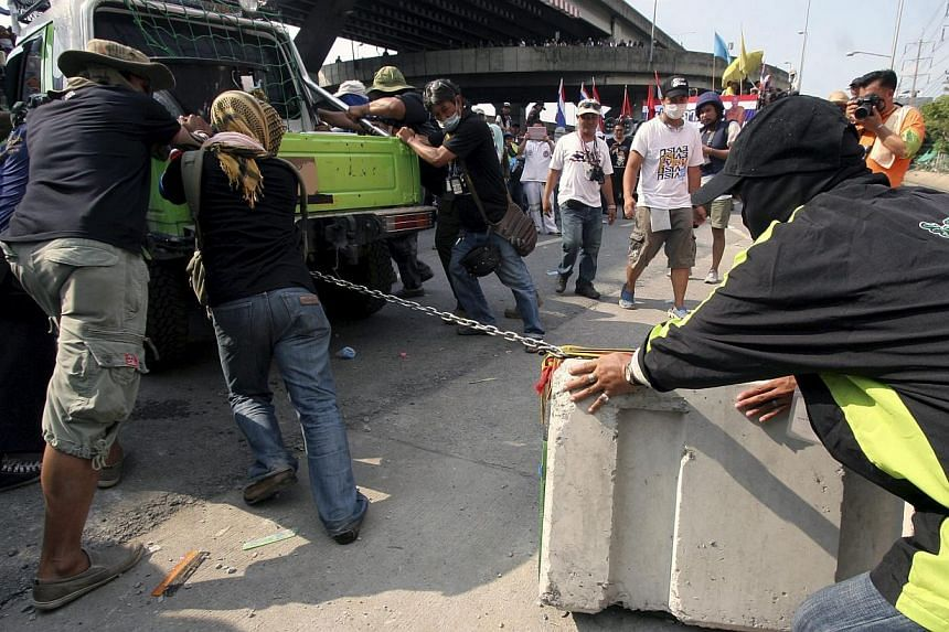 Thai anti-government protesters remove barricade during a rally at the Police Club in Bangkok, Thailand, on May 10, 2014. -- PHOTO: EPA