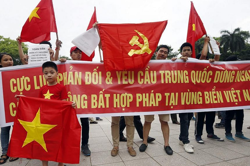 Protesters hold a big banner which reads 'Strongly oppose and demand China to stop Illegal actions in Vietnam waters' during a rally against China in Hanoi, Vietnam, on May 11, 2014. -- PHOTO: EPA