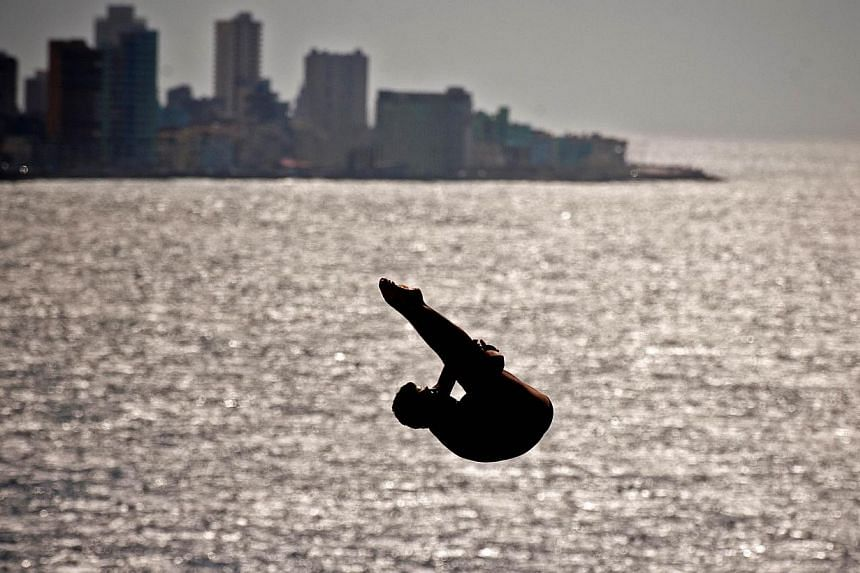A competitor dives from a 27m high platform during the Red Bull Cliff Diving World Series 2014 at the Morro Castle in Havana, on May 10, 2014. -- PHOTO: AFP